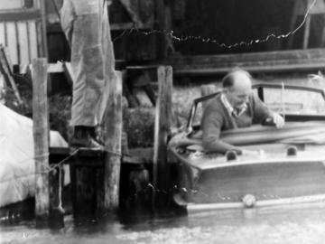 Robert Havemann in seinem Motorboot. Auf dem Steg links neben ihm steht ein Mann.