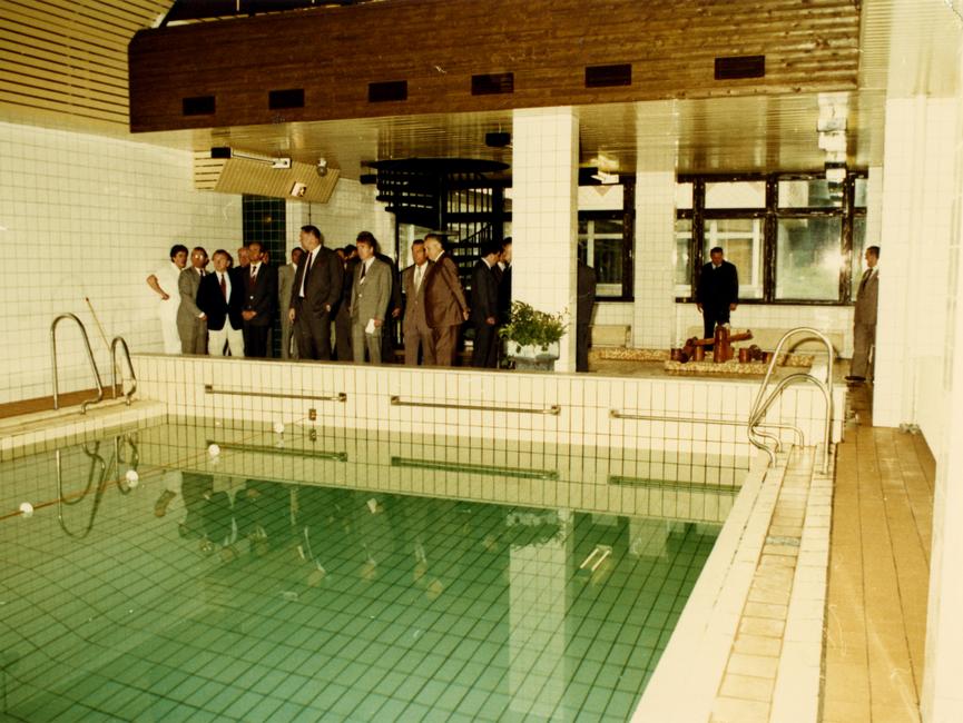 Mehrere Herren im Anzug stehen vor einem Pool und sehen sich um. Es handelt sich um ein farbiges Lichtbild.