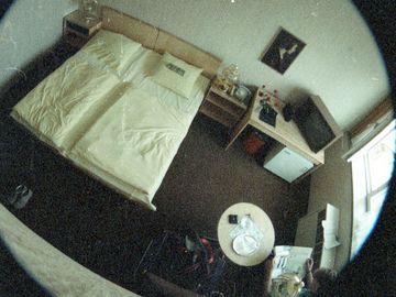 Die vorliegende, in zwei kreisförmige Teilbilder unterteilte, Überwachungsaufnahme zeigt den Innenraum eines Hotelzimmers aus erhobener Perspektive. Das untere Teilbild zeigt in der unteren rechten Ecke eine Person mit grünem Shirt lesend in einem Stuhl an einer kleinen Garnitur sitzend, auf dem freien Stuhl links davon eine Tasche stehend. Ihr gegenüber, in der rechten Ecke des Zimmers, befindet sich ein Tisch mit darauf stehendem Fernseher und Blumen. Darunter ein eingebauter Kühlschrank, links davon ein Doppelbett, umrandet von Beistelltischen. Vor dem Bett findet sich ein Paar Schuhe. Das obere, stark abgeschnittene Teilbild zeigt das Zimmer aus selber Perspektive, die Person hockend vor dem Kühlschrank. Ein verpackter Strauß Rosen liegt auf dem Tisch.