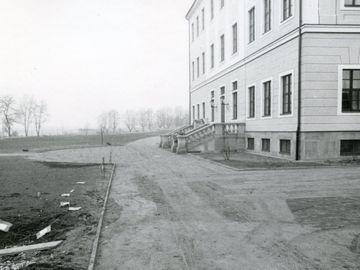 Die Schwarz-Weiß-Fotografie zeigt die Rückseite des Hotels Bellevue in Dresden mit einer zu einem rückwärtigem Eingang führenden Treppe. Das Haus rechts im Bild hat drei sichtbare Stockwerke und wurde mit hellem Sandstein erbaut. Links davon, ausgehend vom Vordergrund und sich beidseitig um das Gebäude ziehend, findet sich ein breiter Sandweg. Gegenüber der Treppe, links im Bild, führt der Weg ab in ein spärlich von Bäumen bewachsenes Brachland.