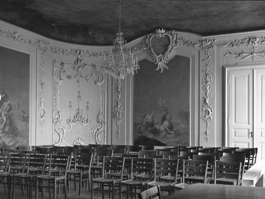 Dieses schwarz-weiße Lichtbild zeigt den 'Gartensaal' des Schloss Nischwitz voll bestuhlt. Der Saal im spätbarocken Stil ist mit zwei großen Wandbildern und Stuck verziert.