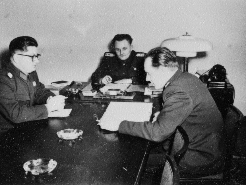 Drei Stasi-Offiziere sitzen an einem Tisch mit Unterlagen.