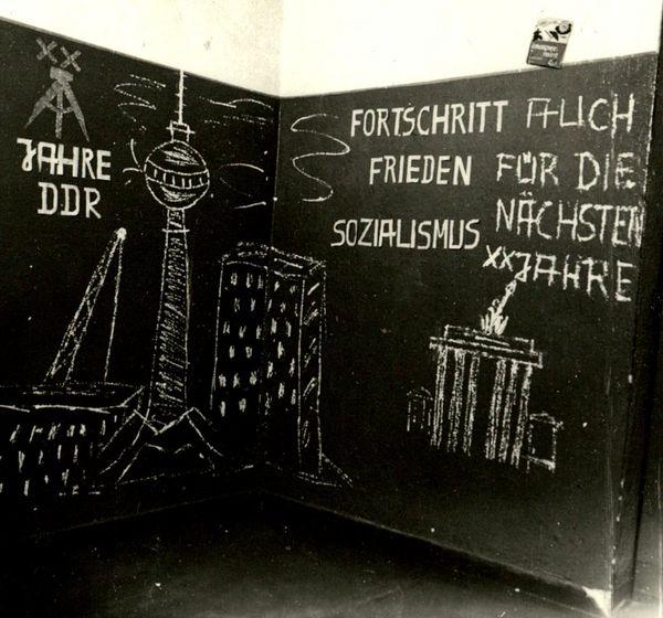 Auf einer Tafel steht mit Kreideschrift 'Fortschritt Frieden Sozialismus auch für die nächsten XX Jahre'. Daneben sind der Berliner Fernsehturm und das Brandenburger Tor abgebildet.