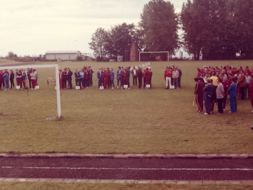 [Das farbige Lichtbild zeigt einen Fußballplatz vor einer Baumgruppe. Gruppenweise sind die Sportler hinter, in den Rasen gerammten, Schildern mit Nummern versammelt.Im linken Bildhintergrund steht eine weiße, eingezäunte Baracke.]