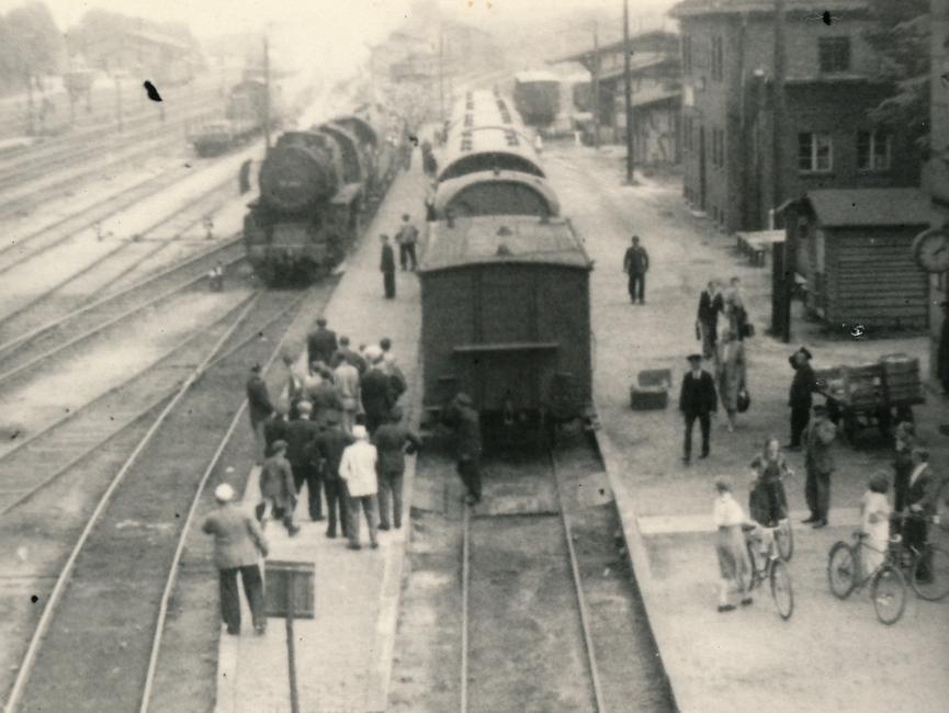 Es handelt sich hierbei um ein Foto vom Bahnhof Belzig auf dem sich ein paar Demonstranten befinden. Auf den Gleisen des Bahnhofs befinden sich drei Züge.
