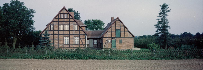 Das Farbfoto zeigt einen Fachwerkhof mit drei Seiten am rande eines Ackers. Das Grundstück des Hofes ist mit einem Zaun begrenzt. Auf dem Grundstück und daneben wächste grüne Vegetation.
