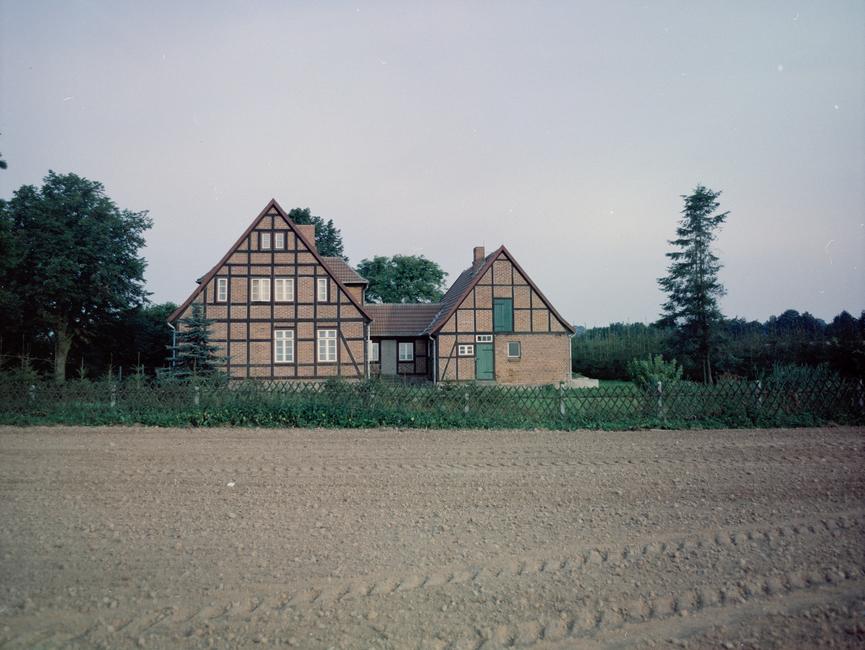 [Frontal auf die Stirnseiten zweier Häuser gerichtetes Farbfoto, das von einem Feld aus aufgenommen wurde. Die beiden Häuser sind  fest miteinander verbunden.]
