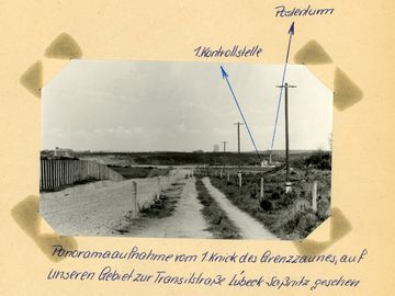 [Das schwarzweiße Lichtbild zeigt einen Blick in die Grenzsicherungsanlagen der DDR. Von links nach rechts sind zu sehen: der Metallzaun, daran angrenzend die geharkte Sandfläche. Ein unbefestigter, aber ausgefahrener Weg wird auf beiden Seiten mit Betonpfeilern markiert. Weiter rechts davon befindet sich ein Grünstreifen, auf dem Elektromasten entlang der Grenzlinie aufgestellt sind. Im Hintergrund liegt eine Kontrollstelle für die Transitstraße. Darum herum sind verstärkt Laternen aufgestellt, ein Wachturm ist in der Nähe. Zwei Stellen wurden auf dem Foto mit blauem Kugelschreiber mittels Pfeilen markiert, die außerhalb des Bildes wie folgt beschriftet wurden:] 1. Kontrollstelle Postenturm [handschriftlich mit blauem Kugelschreiber: Panoramaaufnahme vom 1.Knick des Grenzzaunes, auf unseren Gebiet zur Transitstraße Lübeck-Saßnitz gesehen]
