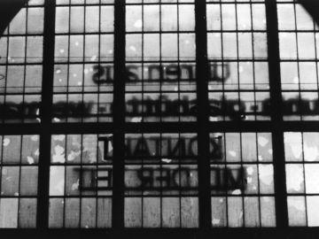 Das schwarz-weiße Lichtbild zeigt die Innensicht auf die große Fensterfläche der Bahnhofsfront des Dresdner Hauptbahnhofs. Der Schriftzug ist seitenverkehrt. Viele der kleinen Fenster sind zerstört.