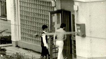 Zwei Männer betreten nacheinander ein Gebäude mit der Hausnummer 26.