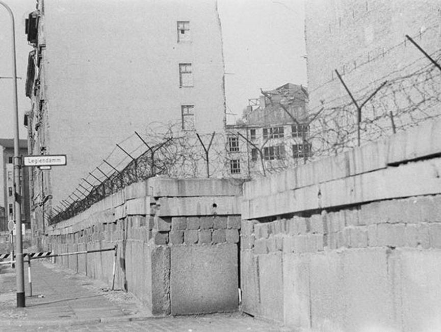 Abgebildet ist der Blick auf die Berliner Mauer vom Westteil der statt. Auf einem Straßenschild ist deutlich 'Legiendamm' zu lesen.