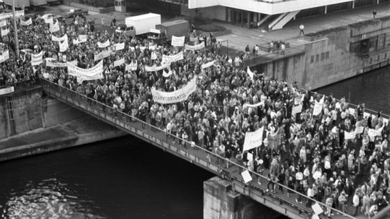 Foto von einer erhöhten Position eine Brücke über die Spree in Berlin. Darauf befinden sich mehrere hundert demonstrierende Menschen, die Transparente mit sich führen. Die Losungen darauf sind nicht zu entziffern. Im Hintergrund ist ein kleiner Teil des Palastes der Republik zu erkennen.