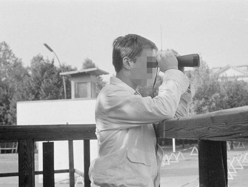 Auf dem schwarz-weißen Lichtbild sieht man einen Mann bis zur Hüfte im Profil auf einer Aussichtsplattform, der durch ein Fernglas sieht.