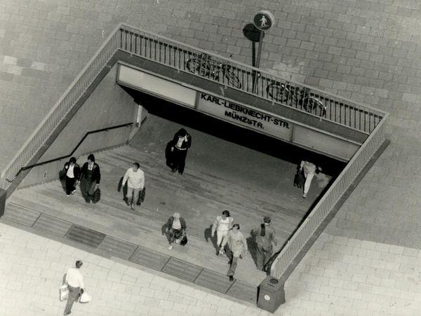 [Auf dem schwarzweißen Lichtbild lassen sich sehr gut einige Menschen erkennen, die die Treppen zur U-Bahnstation hinunter- oder heraufgehen. Auf dem Schild über den Treppen  ist zu lesen 'Karl-Liebknecht-Str. Münzstr.'.]