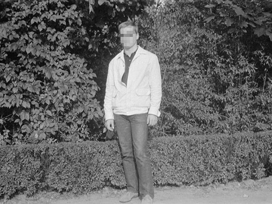 Die Frontalaufnahme zeigt einen Mann in heller Jacke und dunkler Hose vor einer Hecke. Es handelt sich um ein schwarz-weißes Lichtbild.