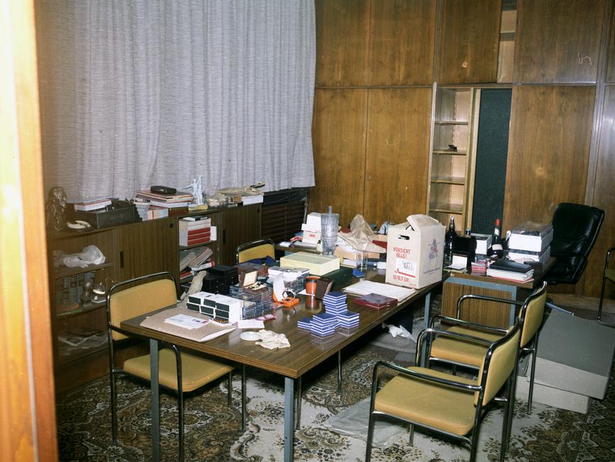 Das Bild zeigt einen Konferenzraum, in dessen Mitte ein großer Tisch mit mehreren Stühlen steht.