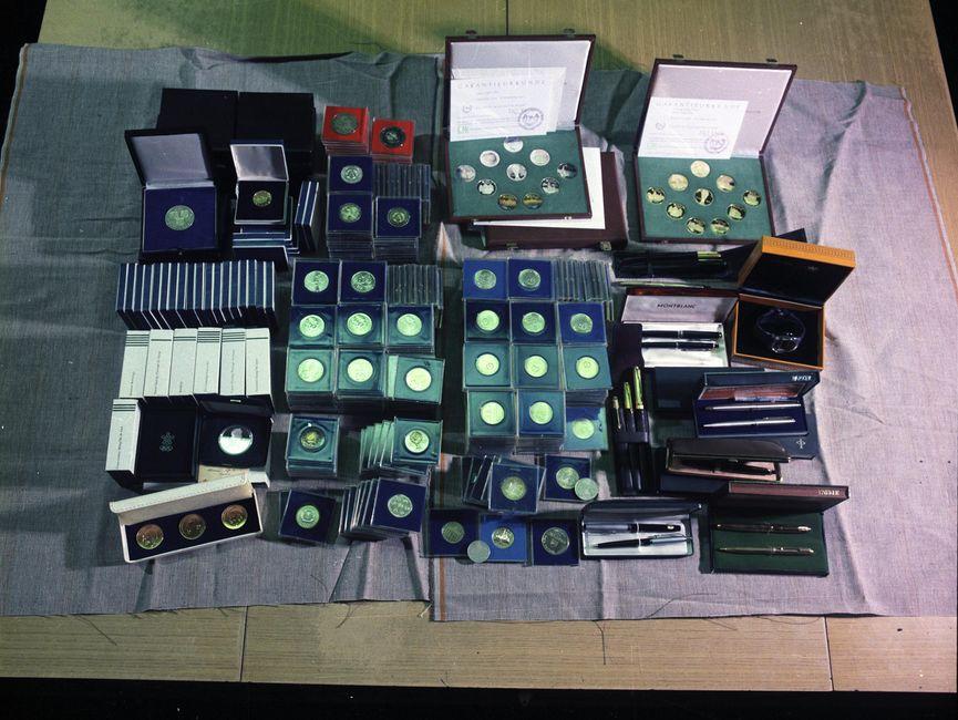 Die Aufnahme zeigt einen Teil eines großen Tisches. Darauf befinden sich einige für die Aufnahme drapierte Gegenstände: weit über 100 Schachteln mit Münzen oder Orden und einige Etuis mit Kugelschreibern