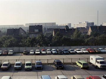 Eine farbige Weitwinkelaufnahme zeigt einen Betonparkplatz vor Einfamilienhäusern im Grünen, im Bildhintergrund sind Hochhäuerreihen zu erkennen. Auf dem Parkplatz sind ordentlich senkrecht geparkte Reihen von verschiedenen Pkw-Modellen und in verschiedensten Farben zu sehen. Dazwischen gibt es ofetmals Lücken, die auch deutlich größer Ausfallen können.