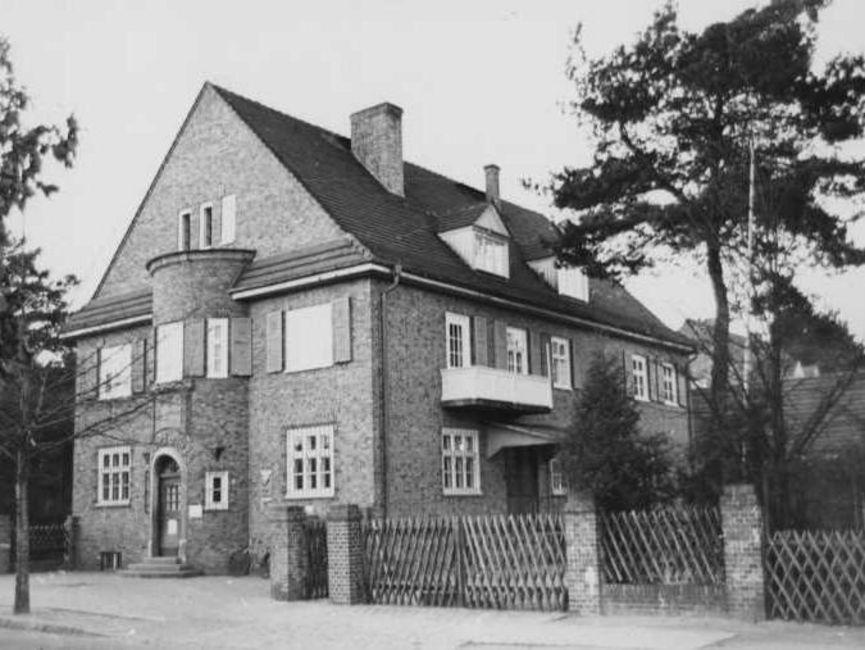 Zu sehen ist ein Backsteingebäude, zwei Etagen mit Spitzdach und Erker mit Eingangstür an der Schmalseite. Hinter einem Jägerzaun rechts am Haus liegt ein weitere EIngang und einige Nadelhölzer.