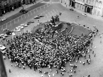 Das Schwarzweißfoto zeigt einen Blick auf den Altstädter Ring in Prag in nordwestlicher Richtung. Das Bild ist von oben aufgenommen, vermutlich vom Turm des altstädtischen Rathauses aus. In der Mitte des Platzes ist das Jan-Hus-Denkmal zu sehen. Es ist zum Teil mit Transparenten behängt, einzelne Menschen sitzen auf dem Sockel. Davor, in Richtung Süden, hat sich eine große Menschentraube versammelt, die in Richtung des Denkmals blickt. Vermutlich hält dort jemand eine Rede.
