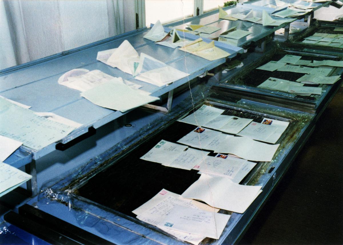 Das farbige Lichtbild zeigt eine Strecke der Brieföffnung. Auf der oberen Ebene sind viele aufgereihte offene Briefumschläge zu sehen. Auf der unteren Ebene sind teilweise die Briefinhalte auf den Umschlägen verteilt. Das Positiv wurde manuell rekonsturiert, im linken Drittel verläuft eine vertikale Risskante.