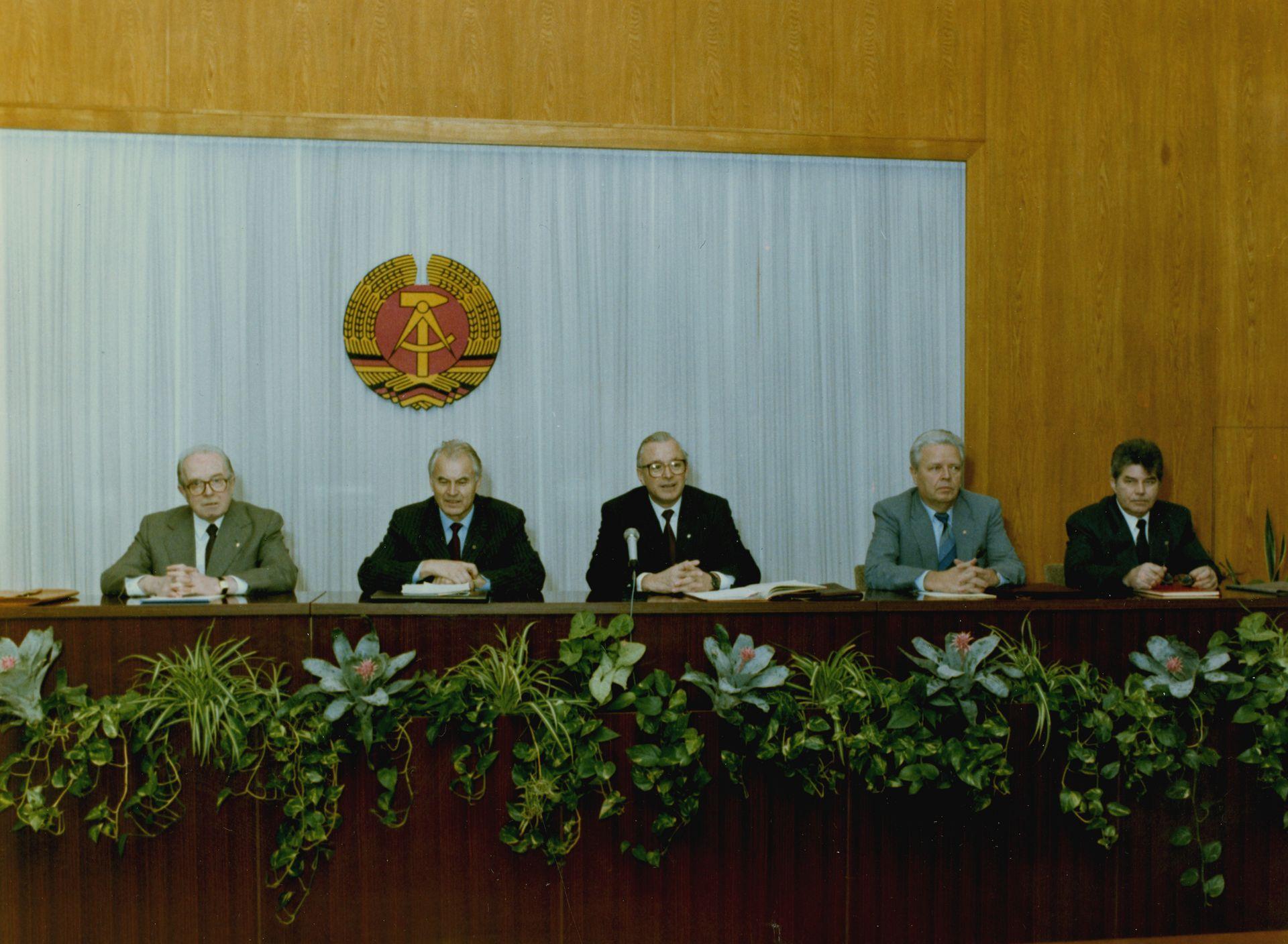 Das Bild zeigt fünf Männer, die auf einem Podium sitzen. Im Vordergrund sind Blumen zu shen, die sich in Blumenkästen befinden. Im Hintergund ein großes DDR-Wappen vor einem weißen Hintergrund.