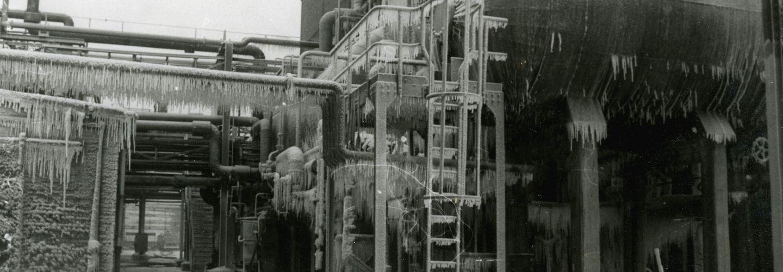 [Auf der schwarz-weiß Fotografie ist ein Teil eines Gebäudes auf einem Industriegebiet zu sehen. An dem Gebäude entlang verlaufen einige Rohre. Unter den Rohren ist ein Durchgang zu erkennen. Rechts vor dem Gebäude ist ein waagerechter Tank angebracht. Zum Tank hinauf führt eine Leiter mit Schutzvorrichtung. Unten rechts auf der Fotografie ist ein Seil vermutlich zur Abtrennung des Bereiches angebracht worden. Daran sind einige Hinweiswimpel mit Ausrufezeichen befestigt. Das Foto ist im Winter aufgenommen worden, da auf dem Boden Schnee zu erkennen ist und der Tank, die Leiter und die Rohre mit vielen Eiszapfen überzogen sind.]