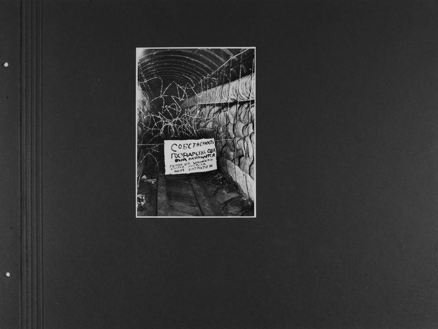 [Das Lichtbild zeigt einen langen Tunnelgang, der auf beiden Seiten gestapelte Jutesäcke hat. Der Eingang ist durch Stacheldraht auf ganzer Höhe versperrt. Davon hängt ein Schild, auf dem in schwarzer Farbe zuerst mit kyrillischen Buchstaben sowie darunter in Deutscher Sprache 'Eigentum der Vereinigten Staaten Amerika; nicht eintreten' geschrieben steht.]