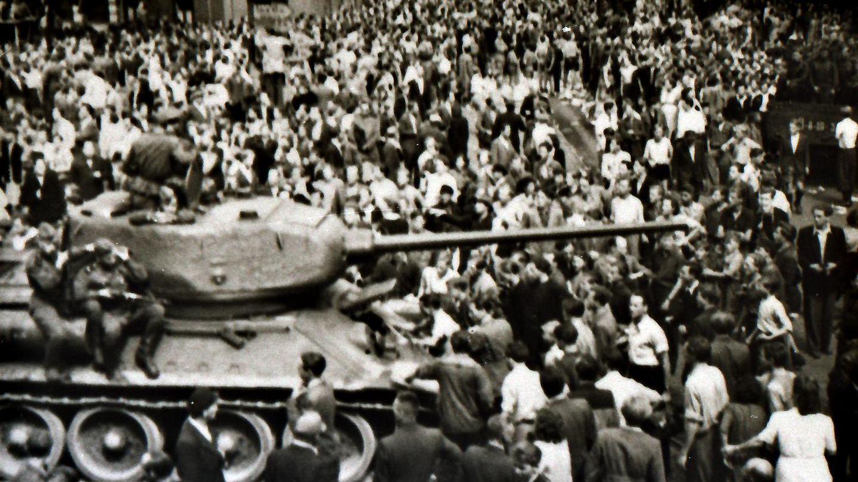 Das Schwarz-Weiß-Bild zeigt, wie Demonstranten einen sowjetischen Panzer blockieren, auf dem sich mehrere Soldaten befinden.