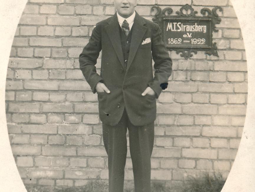 Das ovale Lichtbild ist schwarz-weiß und zeigt einen Jungen im Dreiteiler Anzug. Er steckt die Hände in die Hosentasche, blickt frontal in die Kamera. Hinter ihm steht eine Ziegelmauer, auf der ein Schild 'M. T. Strausberg e.V.; 1962-1922' angebracht ist.