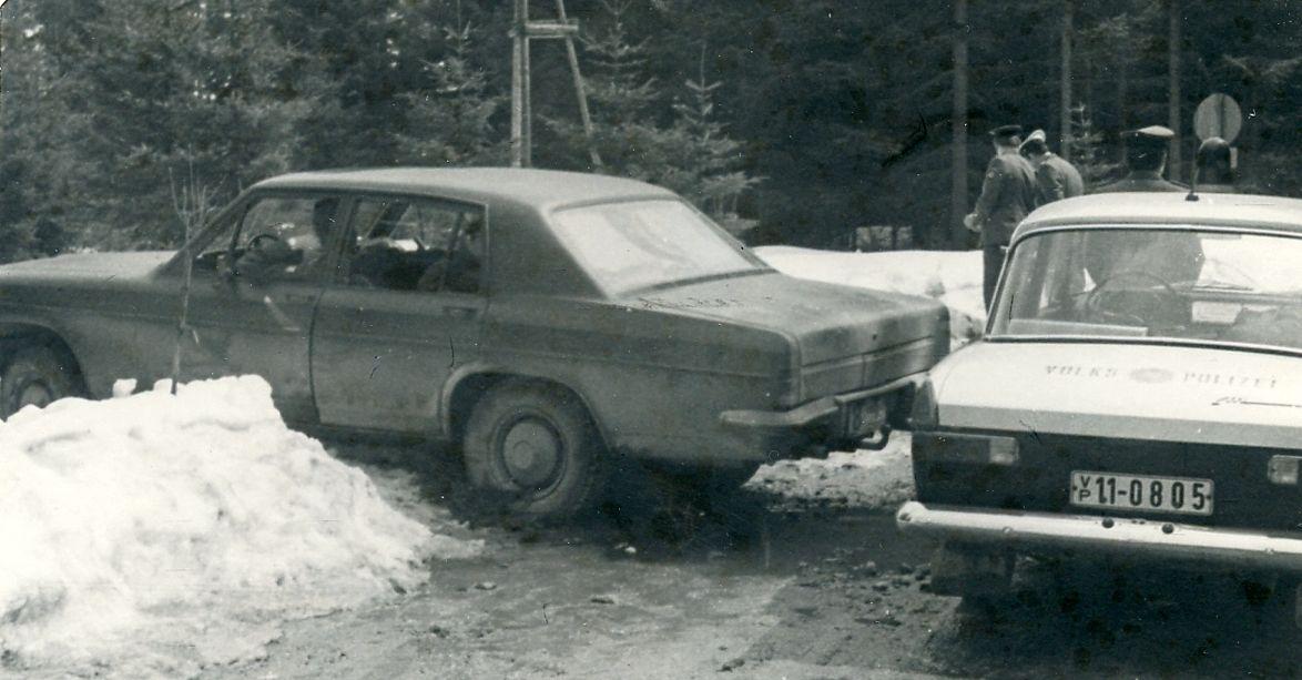 Das Bild zeigt ein Fahrzeug, das in einer Schneewehe feststeckt. Direkt dahinter befindet sich ein Fahrzeug der Volkspolizei.