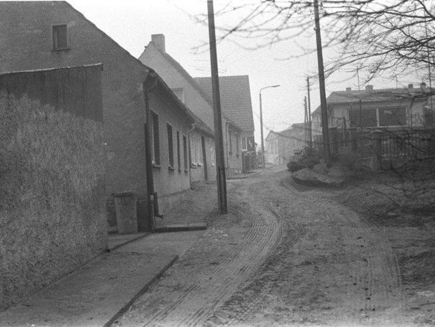 Auf dem schwarz-weißen Lichtbild ist eine unbefestigte Gasse zu sehen, die zwischen den Reihen von Einfamilienhäusern ohne Vorgärten verläuft.