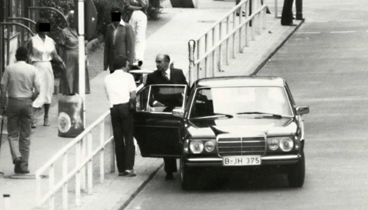 Schauspieler Robert Brown steht bei den James-Bond-Dreharbeiten am Checkpoint Charlie neben einem Auto und spricht mit einer anderen Person