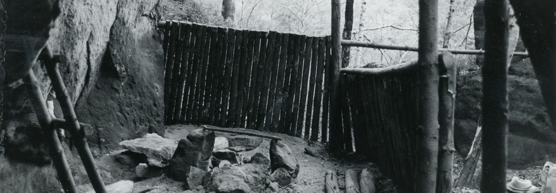 Hierbei handelt es sich um eine Schwarzweißfotografie des Ausblickes aus dem Inneren der Boofe. Man blickt nach vorne und zur rechten auf einen hüfthohen Zaun, hinter dem Baumwipfel zu erkennen sind, links befindet sich die Felswand. Auf dem Boden ist eine Feuerstelle aufgebaut, neben der Holzscheite und Felsbrocken lagern, während links eine kleine Leiter am Gestein angelehnt steht.