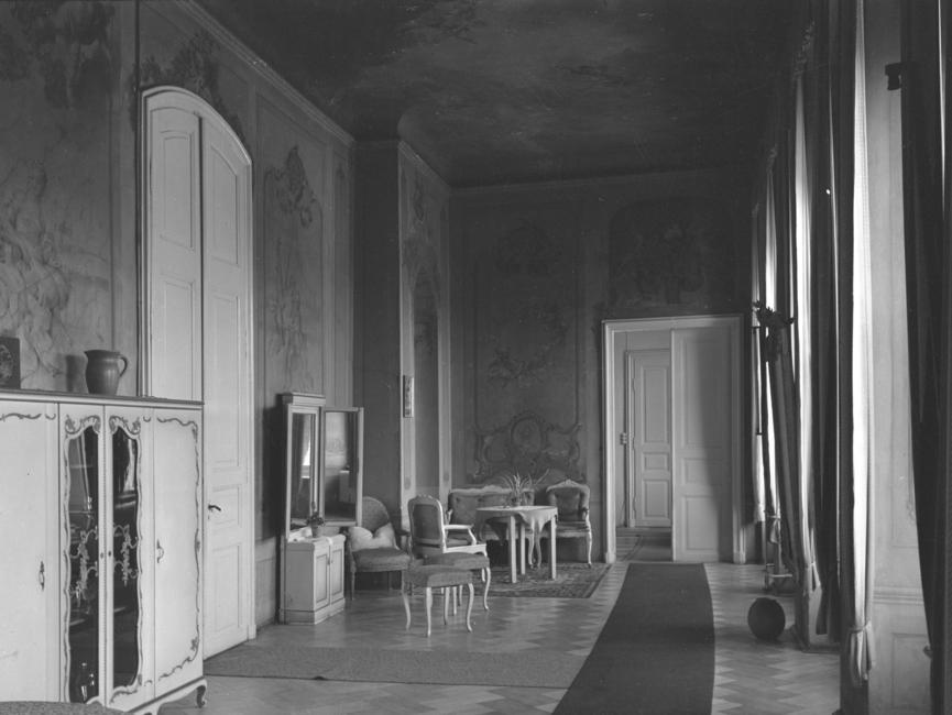 Das langgezogene Durchgangszimmer ist reich an Fresken und ist nur mit wenig Möbelstücken (eine Sitzgruppe, einzelne Hocker sowie zwei Kommoden) versehen, wie auf dem schwarz-weißen Lichtbild zu sehen ist. Der Parkettboden wird durch zwei lange schmale Teppiche geschont.