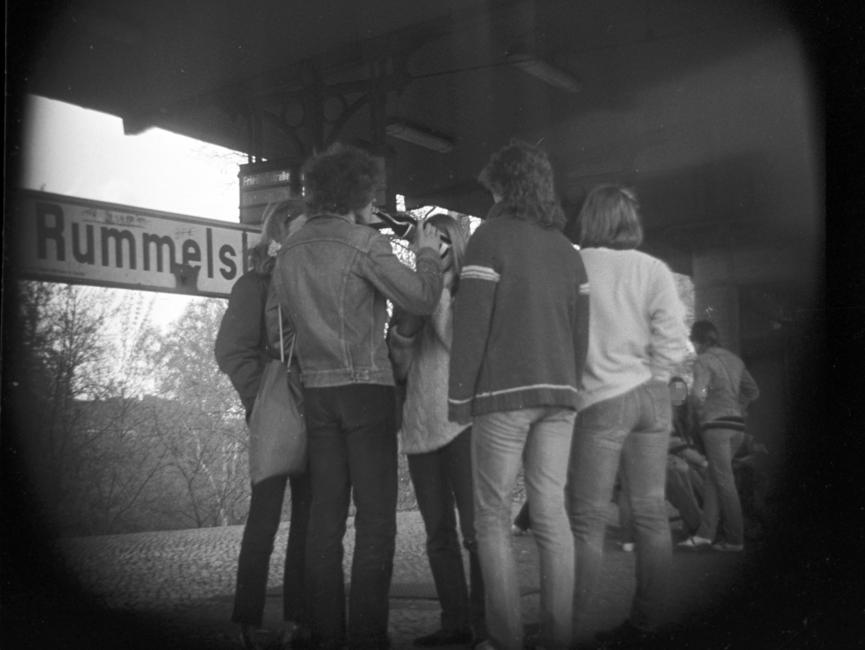 Das schwarz-weiße Negativ zeigt in der Bildmitte fünf Personen, die gesprächig in einer Runde zusammenstehen. Eine der Personen trinkt etwas aus einer Flasche. Sie befinden sich auf dem Bahnhof Berlin-Rummelsburg, was anteilig am Stationsschild hinter ihnen zu lesen ist. Im Hintergrund ist eine weitere Personengruppe zu sehen, die sich überwiegend auf die Sitzplätze niedergelassen haben. Aufgrund der verdeckten Bildaufnahme wirkt der Bildfokus rund, die Ecken sind schwarz.