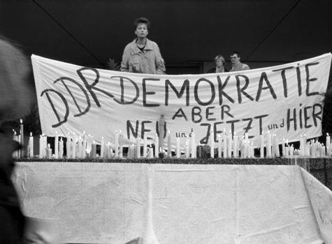 Auf einer Mauer stehen viele brennende Kerzen in einer Reihe. Dahinter ist ein Transparent mit der Losung 'DDR Demokratie aber Neu und Jetzt und Hier' zu lesen. Hinter dem Transparent befinden sich drei Personen.
