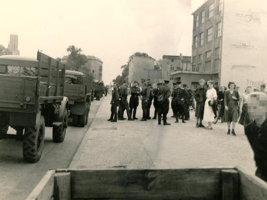 Diese Aufzeichnung zeigt sowjetische Soldaten, welche 'Das Haus der Freundschaft' in Rathenow sichern. Auf der linken Seite der Aufzeichnung befindet sich eine Straße auf der vier sowjetische Truppentransportfahrzeuge parken und auf der rechten Seite befinden sich ein paar Zivilisten.