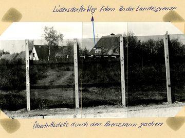 [Hinter dem Grenzzaun wurde der Grünstreifen mit angrenzenden Einfamilienhäusern fotografiert. Ein unbefestigter Weg führt in Richtung der Häuser (dort an einer Schranke endend) sowie an den Grenzzaun. Es handelt sich um ein schwarzweißes Lichtbild, auf dem mit blauem Kugelschreiber per Pfeil eine Markierung vorgenommen wurde. Die Beschriftung folgt außerhalb des aufgeklebten Fotos auf Papierblatt:] Lüdersdorfer Weg Ecken An der Landesgrenze  [handschriftlich mit blauem Kugelschreiber: Übertrittsstelle durch den Grenzzaun gesehen]