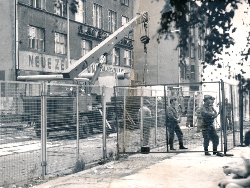 Das schwarz-weiße Lichtbild zeigt das Gebäude der 'Neuen Zeit' vom Union Verlag, davor steht ein Schwerlastkran. Hinter der Abgrenzung durch einen Bauzaun stehen mehrere Männer, teils uniformiert und teils mit Bauhelmen. Das Foto war mittig zerrissen worden und ist nun manuell rekonstruiert.