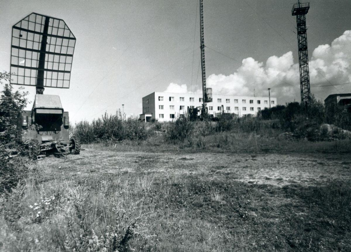 Das Bild zeigt eine Bergkuppe, auf der sich mehrere Gebäude und funktechnische Anlagen befinden.