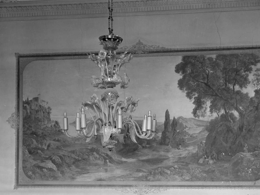 Auf dem schwarz-weißen Lichtbild ist ein Kronleuchter zu sehen, der vor einem gemalten Landschaftsbild hängt. Am Deckenübergang ist Stuck angebracht.