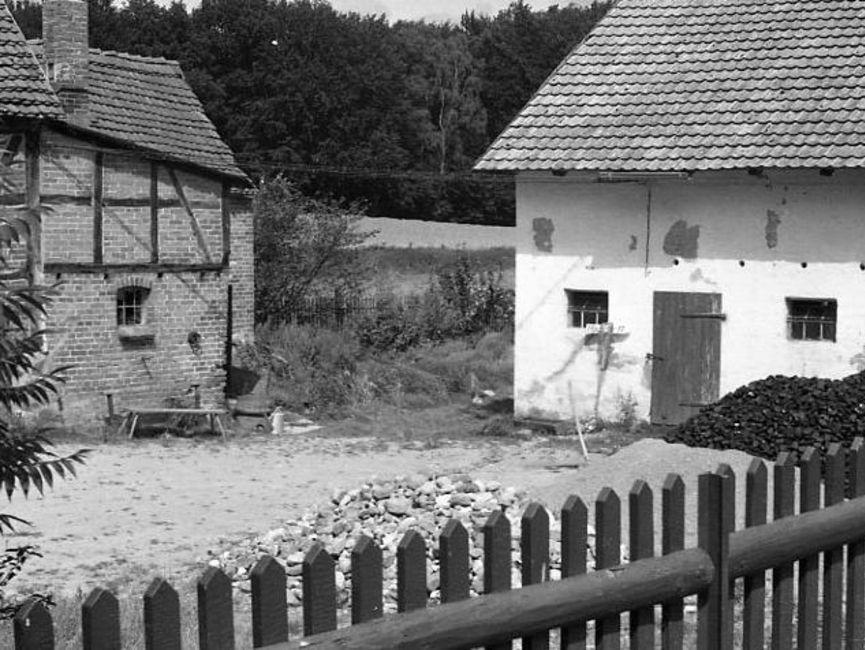 Über einen Zaun hinweg wurde in den Innenhof zwischen zwei Häusern fotografiert. Das rechts stehende Haus wurde an diversen Stellen verputzt, davor liegen drei große Haufen, getrennt nach Gestein und Sand. Links steht ein Fachwerkhaus, das anteilig zu sehen ist. Es handelt sich um ein schwarz-weißes Lichtbild.