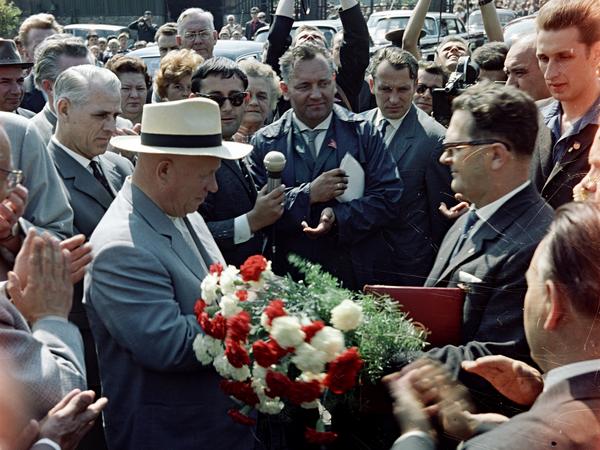 Chruschtschow steht in der Bildmitte, er trägt einen Hut und blickt zu Boden. Um ihn herum steht eine Menge aus Menschen, viele davon vermutlich Angestellte des Werks. Im Vordergrund des Bildes sind applaudierende Hände zu sehen. Ein Mann mit Sonnenbrille direkt hinter Chruschtschow hält ihm ein Mikrofon entgegen.