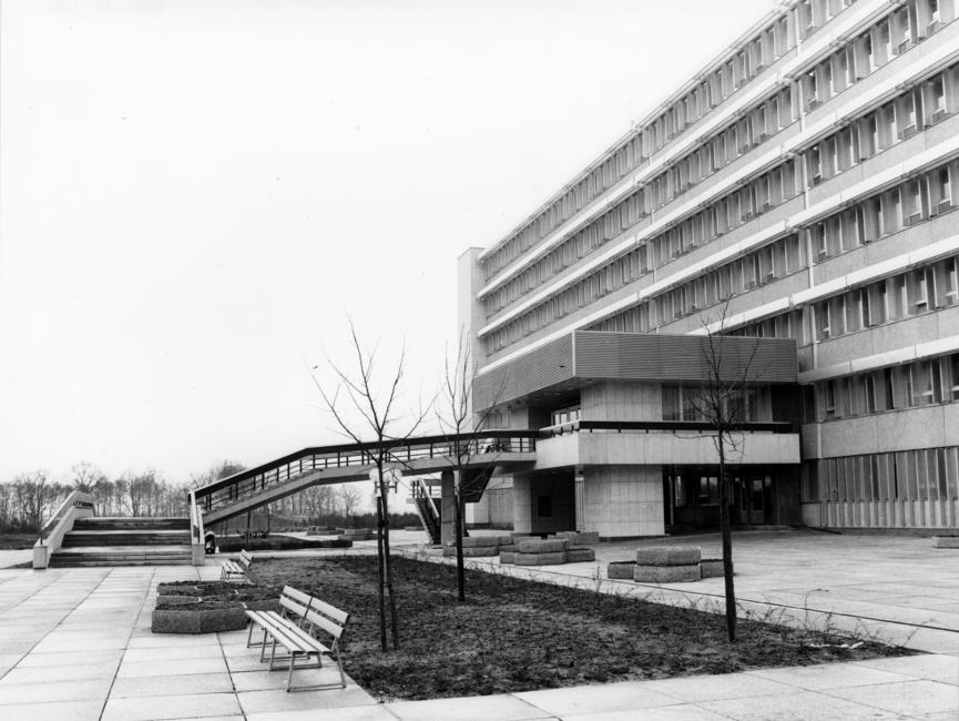 Das Schwarz-Weiß-Bild zeigt einen Teil des Stasi-Krankenhauses in Berlin-Buch. Zu sehen ist der Haupteingang mit einem kleinen Anbau, zu welchem eine Treppe hinaufführt. Im Vordergrund des Bildes ist zudem eine kleine Rasenfläche mit drei kahlen, noch recht kleinen Bäumen zu sehen. Davor steht eine Sitzbank.