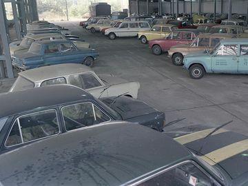 Ein überdachter Betonplatz wurde als Parkplatz für verschiedenfarbige Modelle von Pkws benutzt. Die Autos stehen in Schrägaufstellung und es gibt nur wenige Lücken. Alle Scheibenwischer wurden von den Frontscheiben weggeklappt. Auf der linken Bildseite sind ein paar Stützpfeiler sowie ein Maschendraht zu sehen, doch auch dahinter stehen Kraftfahrzeuge. Es ist ein weitwinklig aufgenommenes, farbiges Lichtbild und wurde von leicht erhöhter Position aufgenommen.