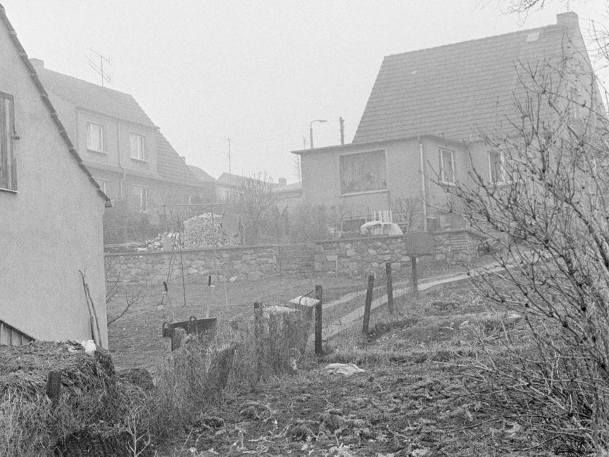 Das schwarz-weiße Lichtbild ist ein bergaufführender, unbefestigter Pfad zu sehen, an dessen Ende wieder das Einfamilienhaus mit Spitzdach steht.