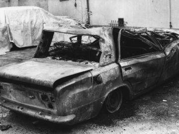 Das Schwarz-Weiß-Bild zeigt ein völlig ausgebranntes Fahrzeug. Links davon steht ein weiteres Fahrzeug, das mit einer Plane abgedeckt wurde.