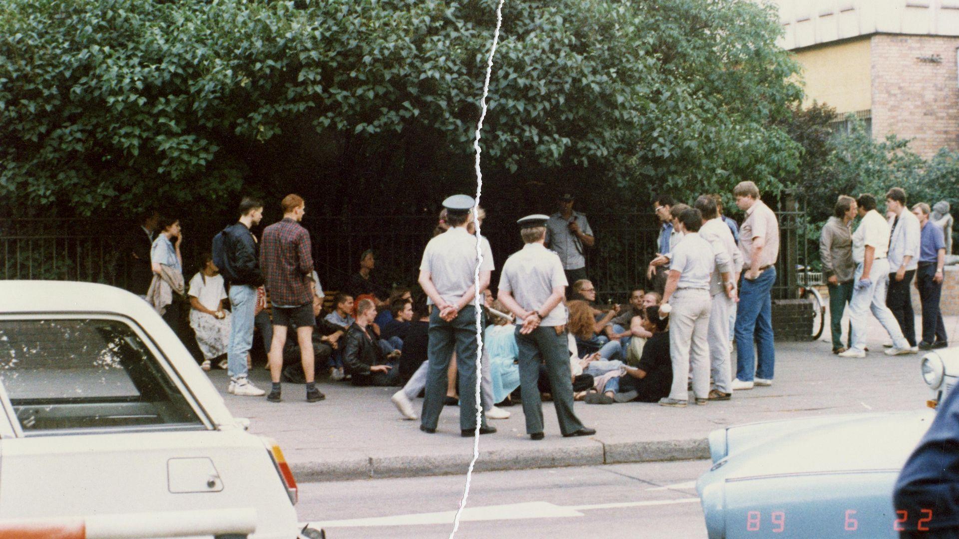 Eine Personengruppe sitzt auf einem Bürgersteig direkt vor einem Zaun. Sie werden umringt von Volkspolizisten sowie einigen steif wirkenden Herren in ordentlichem Zivil. Das farbige Lichtbild wurde manuell rekonstruiert, in der Mitte ist der vertikale Riss sichtbar.