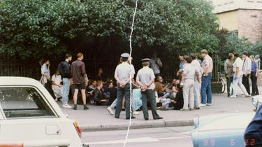 Eine Personengruppe sitzt auf einem Bürgersteig direkt vor einem Zaun. Sie werden umringt von Volkspolizisten sowie einigen steif wirkenden Herren in ordentlichem Zivil. Das farbige Lichtbild wurde manuell rekonstruiert, in der Mitte ist der vertikale Riss sichtbar.]
